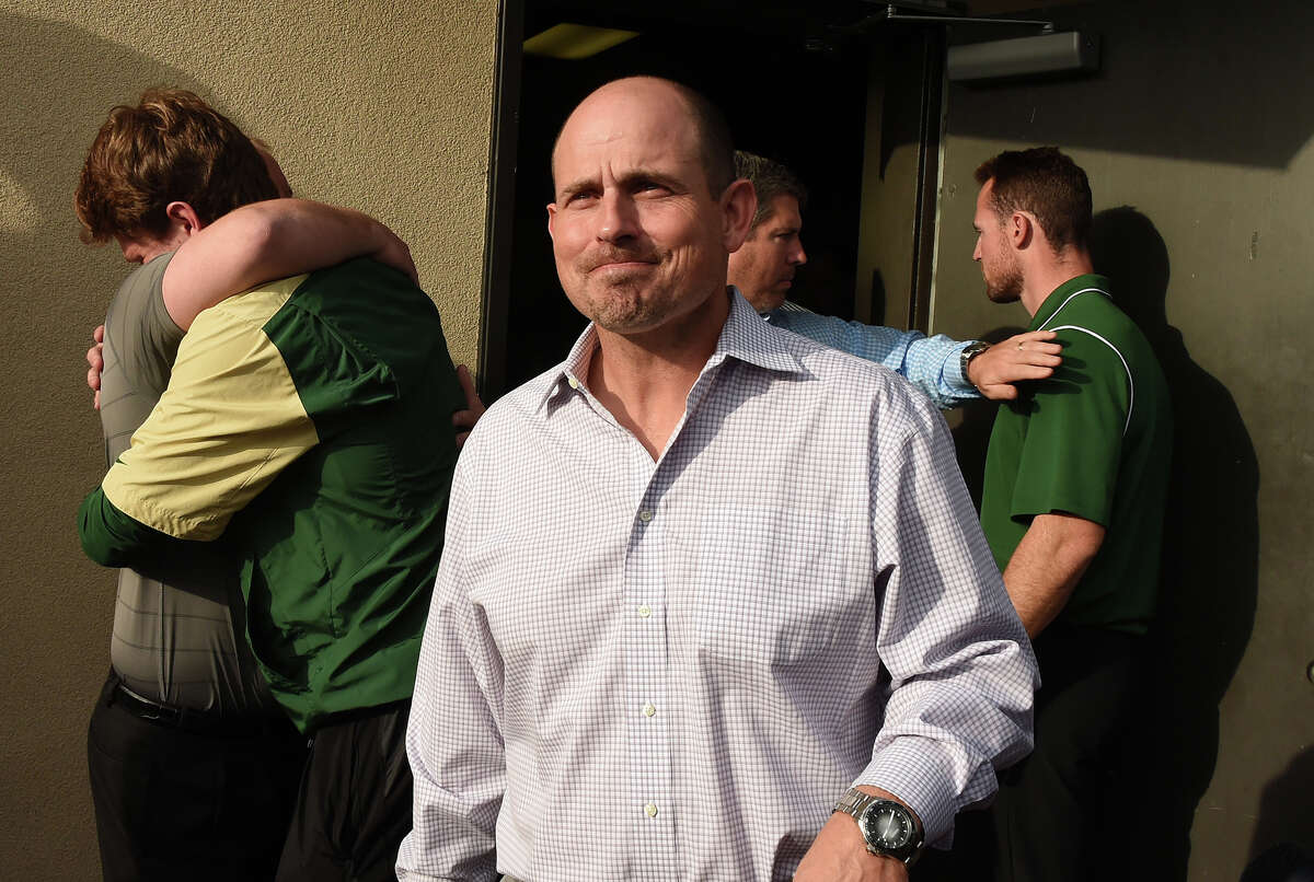 UAB head football coach Bill Clark leaves the meeting with school president Ray Watts as players and coaches hug behind him in the doorway on Dec. 2. UAB is shutting down the football program.
