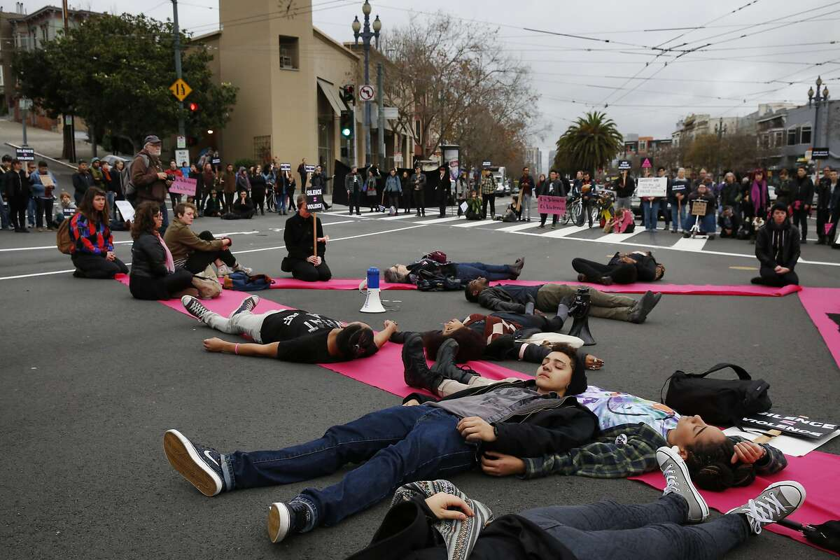 """Tori Porter, 19, center right, lays on her partner Maile Hampton, 20, in silence with others for four and a half minutes in the middle of the intersection at Market and Castro streets during a """"LGBT Rally and March for an End to Police Violence"""" Dec. 24, 2014 in San Francisco, Calif. The group blocked the intersection of Octavia and Market streets where they read the names of some of those killed by police recently. They also held four and a half minutes of silence to symbolize the amount of time Michael Brown's body laid in the street after he was fatally shot by a police officer in Ferguson, Mo. Afterwards, the group marched up Market to Castro street, where they again blocked the intersection, spoke about the issues faced by black queer people and held another four and a half minutes of silence before dispersing."""