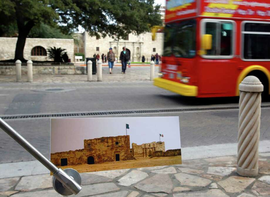 A rendering of the Alamo Long Barracks and the Alamo Church depicting the structures as they would have looked in 1836 is seen in December in front of the building as it looks today. This photo is taken from in front of the Crockett Block Building on the west side of Alamo Street. Photo: William Luther /San Antonio Express-News / © 2014 San Antonio Express-News