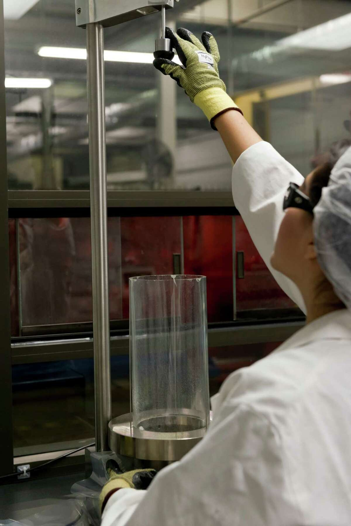 A quality control worker at Houston's Superbag performs a test measuring the strength of plastic film the company uses to make bags.