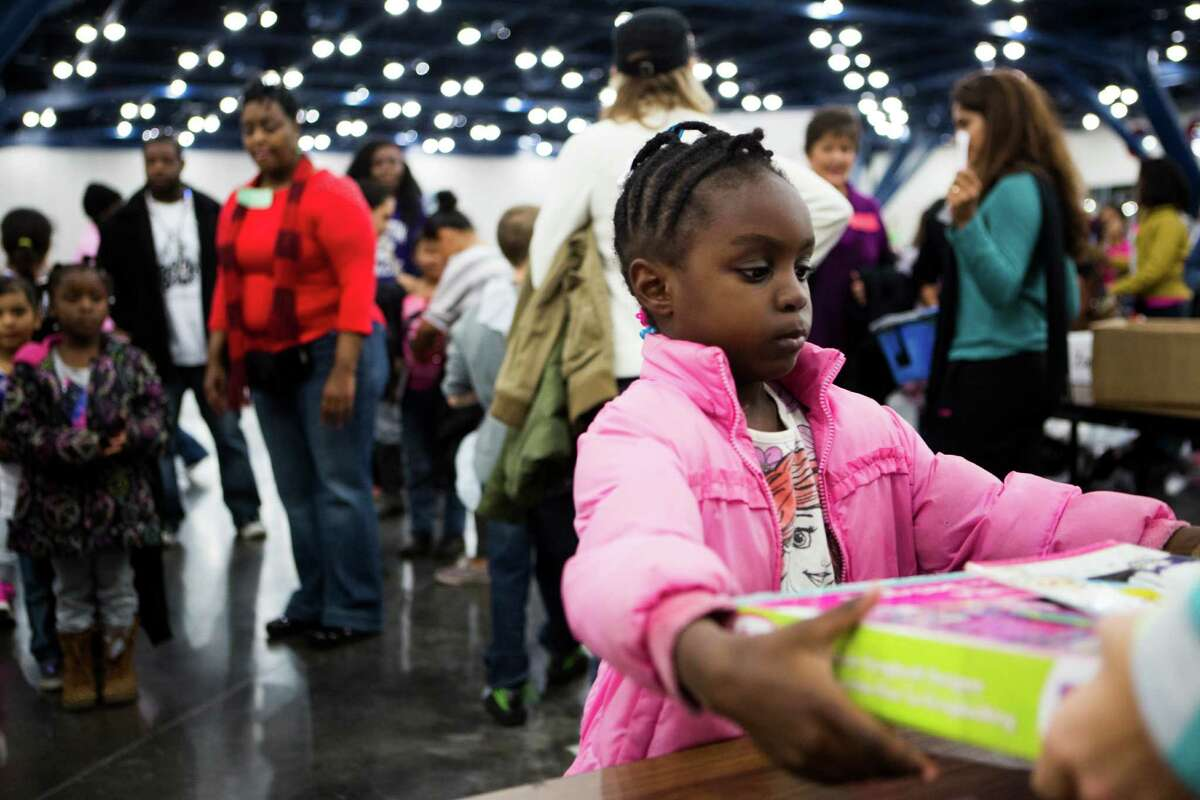 Mariam Diop, 5, of Houston receives a set of stickers for her to play with at the 36th Annual Christmas Eve Big Super Feast 2014 at the George R. Brown Convention Center in Houston, Wednesday, Dec. 24, 2014.