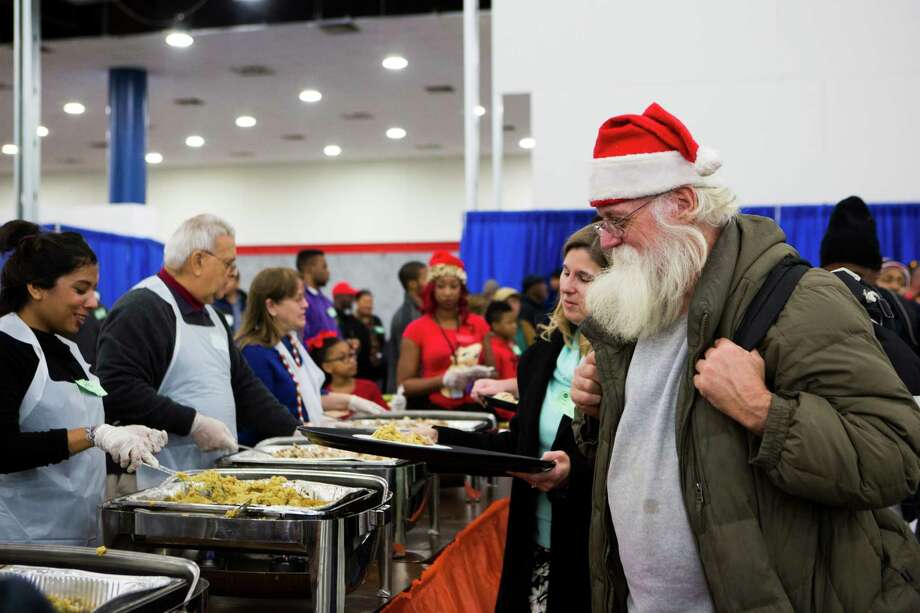 Paul Watkins, 59, right, arrived to the Georgia R. Brown to get a warm meal and food wearing a Santa Claus beard and hat. At his arrival volunteer Melanie Graybill escorted him to get his plate of food ready. The event is the 36th Annual Christmas Eve Big Super Feast 2014 and thousand of members of the community either arrive to enjoy the food, live music and gifts or come to volunteer helping on the different stations. Wednesday, Dec. 24, 2014. Photo: Marie D. De Jesus, Houston Chronicle / © 2014 Houston Chronicle
