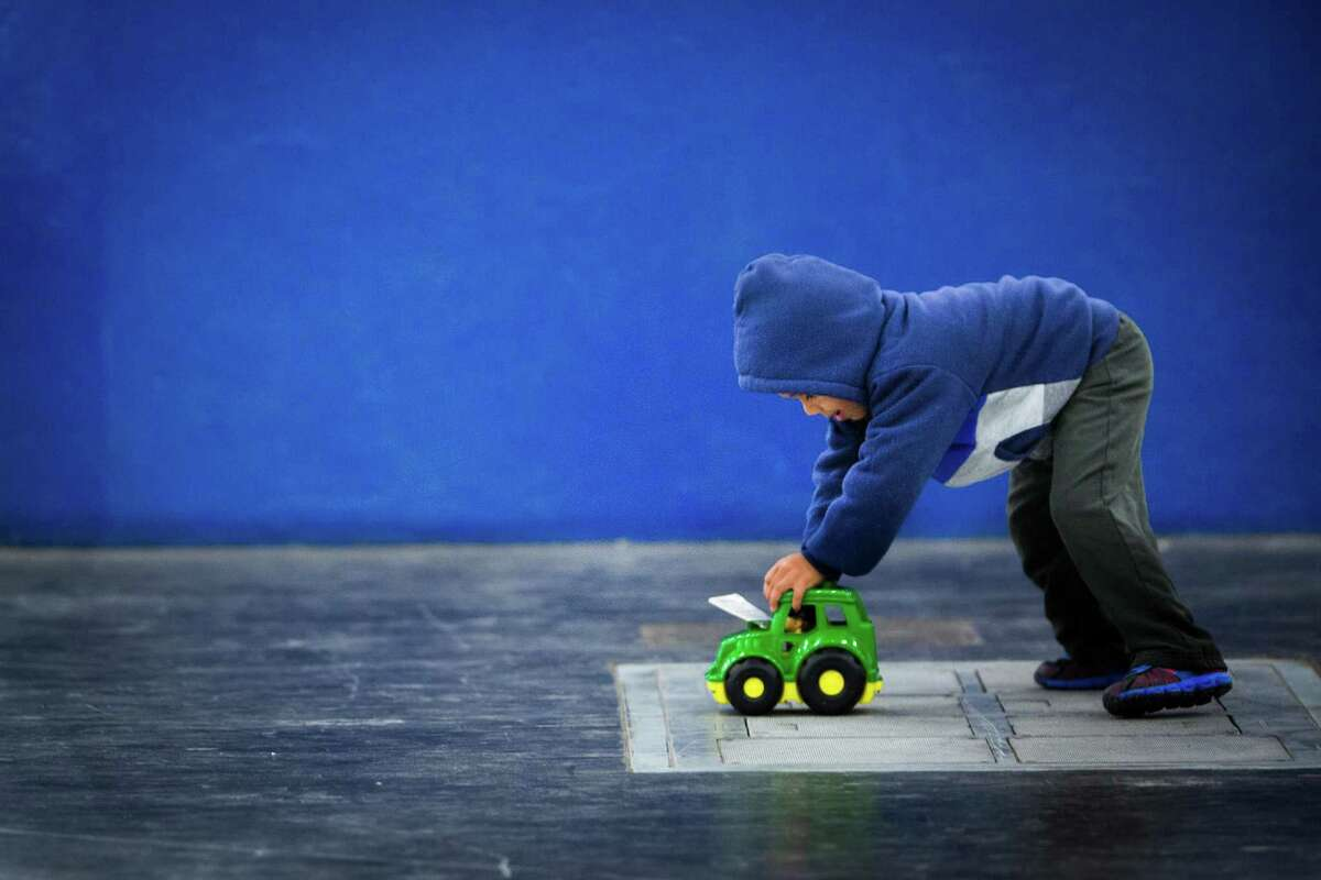 Norwin Benitez, 3, plays with a toy truck he received at the 36th Annual Christmas Eve Big Super Feast 2014 at the George R. Brown Convention Center in Houston, Wednesday, Dec. 24, 2014.