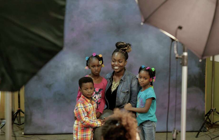 Twanisha Johnson and her children (l to r) Lamonte Kennedy,4, Leonjanae Johnson,6 and Realidy,5 have their free portraits taken during the holiday fair at Castlemont High School in Oakland, Calif. on Saturday Dec. 6, 2014. Photo: Michael Macor / The Chronicle / ONLINE_YES
