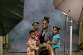 Twanisha Johnson and her children (l to r) Lamonte Kennedy,4, Leonjanae Johnson,6 and Realidy,5 have their free portraits taken during the holiday fair at Castlemont High School in Oakland, Calif. on Saturday Dec. 6, 2014.