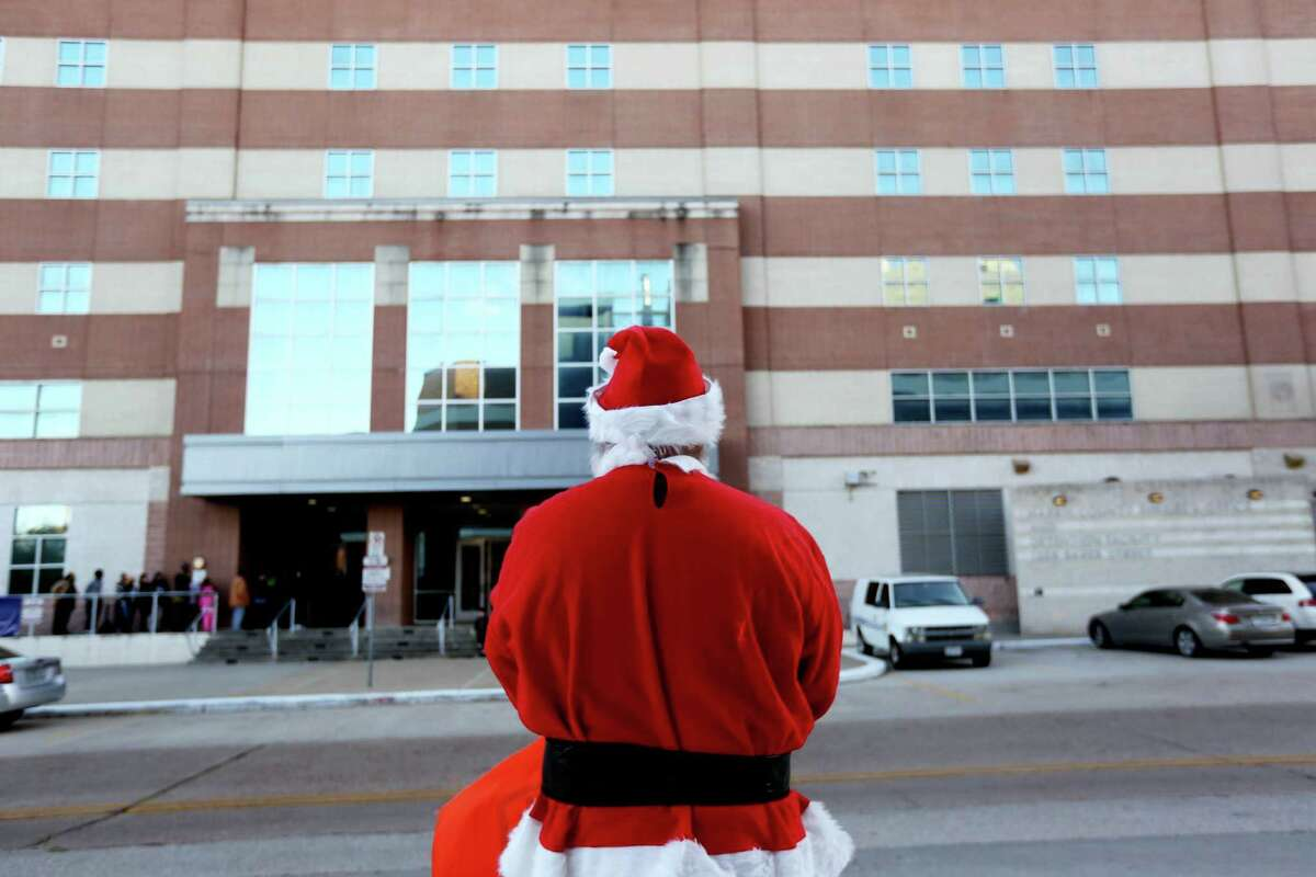 Dave Detcher, playing Santa Claus, waits for children while End Mass Incarceration, an activist group trying to reduce the number of people imprisoned for relatively minor offenses, gives Christmas gifts to children as they leave the Harris County Sheriff's Office and Detention Facility after visiting their incarcerated parents Wednesday, Dec. 24, 2014, in Houston, Texas.