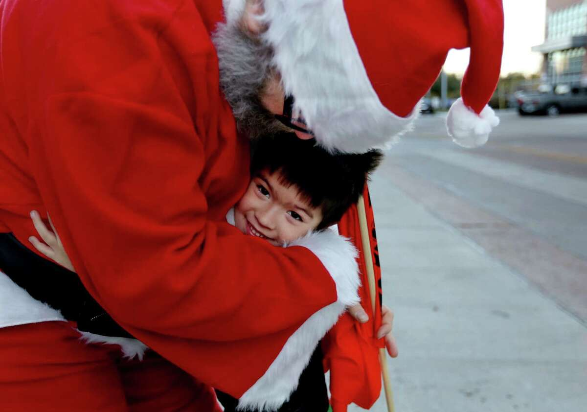 Dave Detcher, playing Santa Claus, gives a hug to Nicholas Cena, five, while End Mass Incarceration, an activist group trying to reduce the number of people imprisoned for relatively minor offenses, gives Christmas gifts to children as they leave the Harris County Sheriff's Office and Detention Facility after visiting their incarcerated parents Wednesday, Dec. 24, 2014, in Houston, Texas. Cena was visiting his mom who is incarcerated.