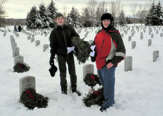 Members of the Schuyler Society, Children of the American Revolution, helped lay wreaths at the Gerald B. H. Solomon Saratoga National Cemetery during the annual Wreaths Across America event on Dec. 13. Society President Christopher Oxaal, left, and Vice President Benjamin Gallant participated. This year the Schuyler Society was one of a dozen community groups that collected 2,200 sponsorships for the wreaths. (Mary Oxaal) Photo: Picasa