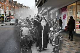 In this digital composite image a comparison has been made of London at Clapham Junction in 1926 (Archive, Topical Press Agency) and Modern Day 2014 (Peter Macdiarmid) at Christmas time.  *** ARCHIVE *** LONDON - NOVEMBER 1926:  Father Christmas arriving at the Arding and Hobbs store on November 2, 1926 in Clapham Junction, London.  (Photo by H. F. Davis/Topical Press Agency/Getty Images) ***MODERN DAY*** LONDON, ENGLAND - DECEMBER 15:  Shoppers walk past Debenhams in Clapham Junction on December 15, 2014 in London, England.  Christmas is an annual religious feast day originally set on December 25 to celebrate the birth of Jesus Christ and is a cultural festival and public holiday celebrated by billions of people around the world.