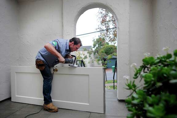 TaskRabbit worker Brian Schrier grinds down the edge of a door that was sticking in its frame at a client's home in Piedmont.