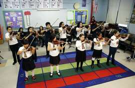 Students at Richard Edwards Elementary School in Chicago learn mariachi-style violin in one of the mariachi music programs that are springing up around the country.