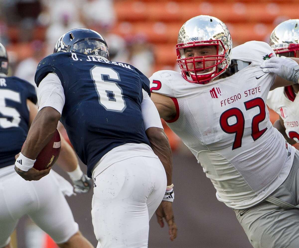 Fresno State defensive lineman Tyeler Davison (92) attempts to grab and tackle Rice quarterback Driphus Jackson (6) in the second quarter of the Hawaii Bowl NCAA college football game, Wednesday, Dec. 24, 2014, in Honolulu. (AP Photo/Eugene Tanner)