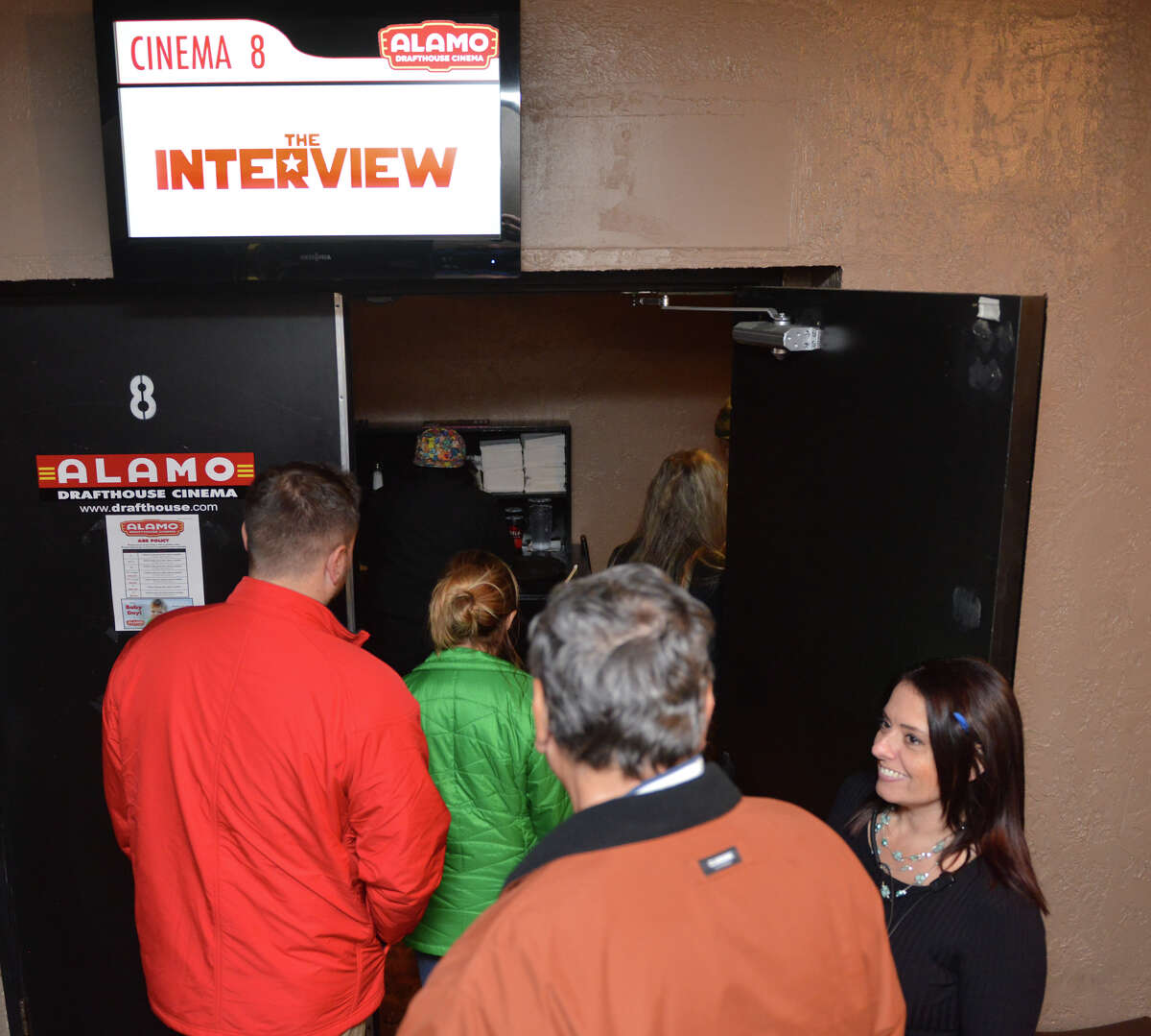 """Westlakes Alamo Drafhouse manager Christe (sp) Schrenk (right) holds the door open for a portion of the sold-out Christmas morning audience of the first San Antonio showing of """"The Interview""""."""