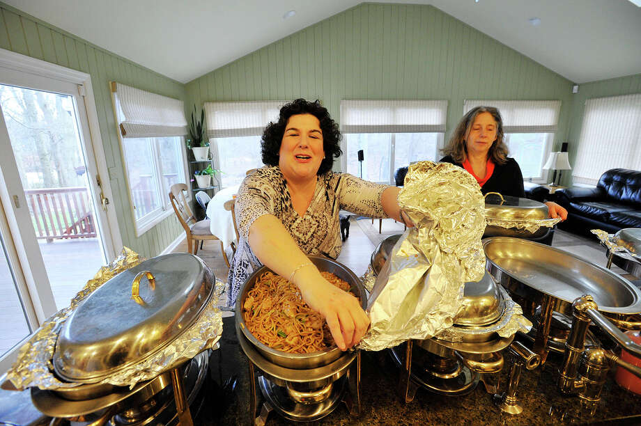 Judy Rayner uncovers the Chinese food before the start of the Greenwich Reform Synagogue holiday open house at Judy and Ed Rayner's home in Riverside Greenwich, Conn., on Thursday, Dec. 25, 2014. This is the second year the Rayners have hosted the interfaith open house. Photo: Jason Rearick / Stamford Advocate