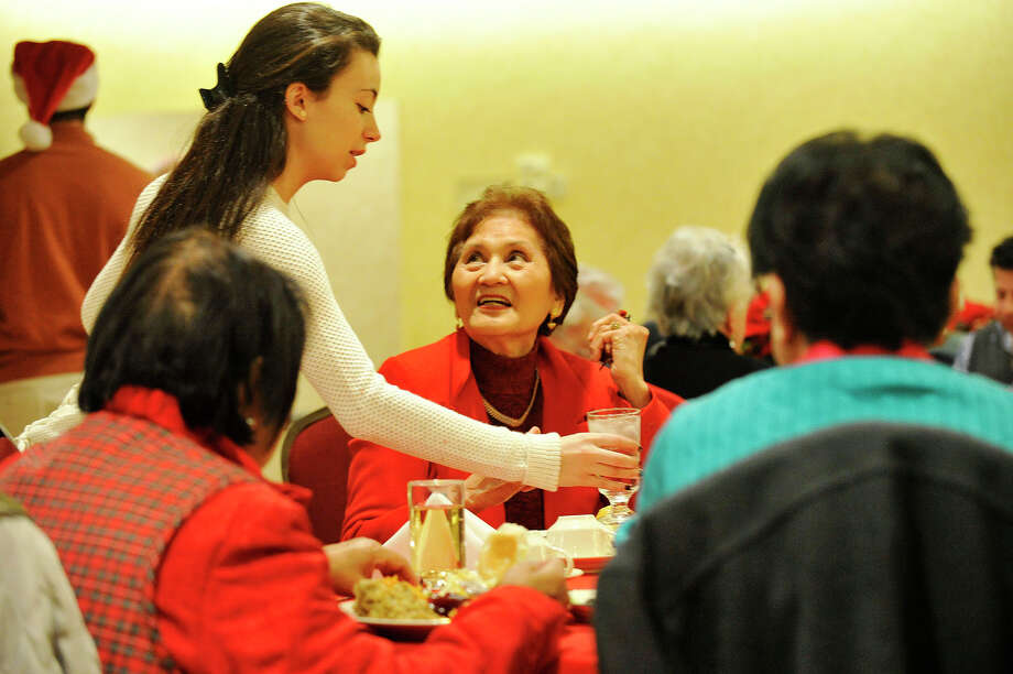 Volunteer Valentina Parker, left, gets water for Soledad Magtibay during the Knights of Columbus community Christmas dinner at their council hall in Greenwich, Conn., on Thursday, Dec. 25, 2014. The Knights of Columbus have been hosting a Christmas Day meal in Greenwich every year for the past 40 years. Photo: Jason Rearick / Stamford Advocate