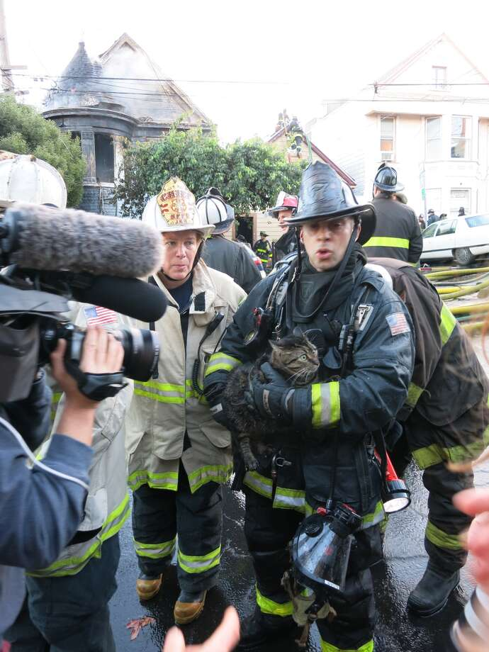Firefighters respond to a three-alarm fire that badly damaged two homes on Thursday, Dec. 25, 2014, in San Francisco's Potrero Hill neighborhood at 245-247 Mississippi. Four adults escaped the blaze without injuries and firefighters rescued two cats, but a pet dog died in the fire. Photo: Paul Herman @HIPinvestor