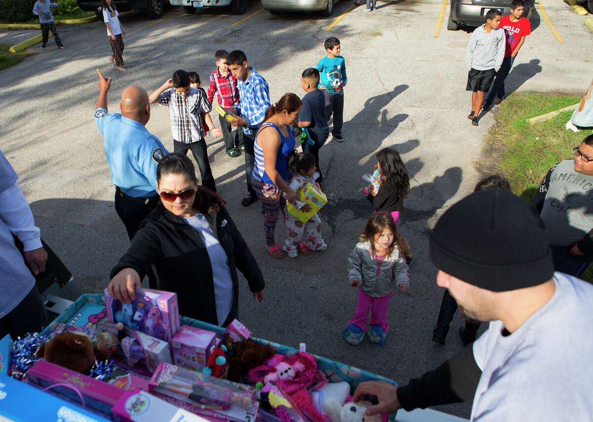 The Latin Fantasy Lowrider Car Club hands out Christmas gifts to families, Thursday, Dec. 25, 2014, in Houston.