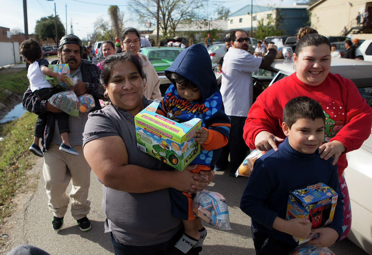 Margarita Campos, center, carries her son, Jiovanni Campos, 2, after getting a gift from the Latin Fantasy Lowrider Car Club, Thursday, Dec. 25, 2014, in Houston.