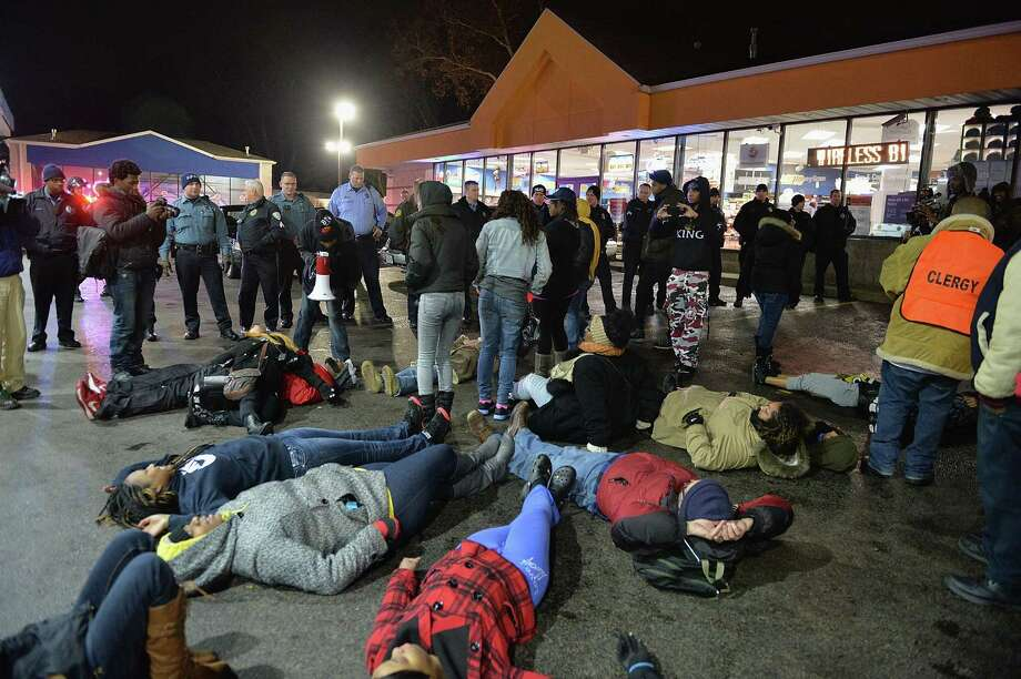 Demonstrators hold a die-in outside the Berkeley, Mo., gas station where Antonio Martin was fatally shot after police say he pointed a gun at them. Photo: MICHAEL B. THOMAS / AFP/Getty Images / 2014 AFP