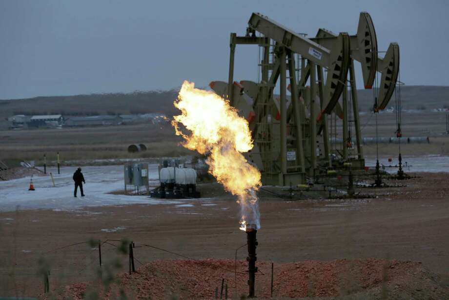 Workers tend to oil pump jacks behind a natural gas flare this month near Watford City, N.D. Photo: Eric Gay / Associated Press / AP