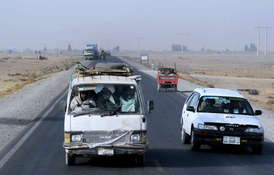 Afghan men crowd into a van approaching Kandahar. The roads are treacherous for foreigners after a violent year in the troubled nation. Photo: ROBERTO SCHMIDT / AFP/Getty Images / PRAKASH SINGH