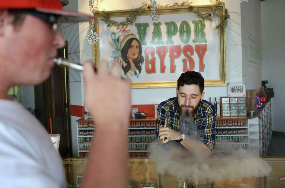 Adam Farrar, assistant manager at Vapor Gypsy, answers questions for customer Josh Eason, 19. The Heights store cards minors.
