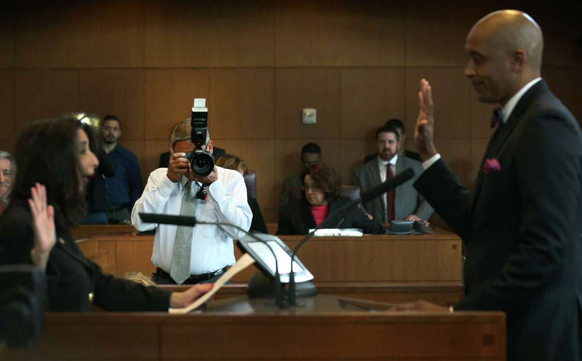 Fred Gonzales, the City of San Antonio Photographer, photographs Alan Warrick being sworn in during a city council meeting. Tuesday, Dec. 16, 2014.