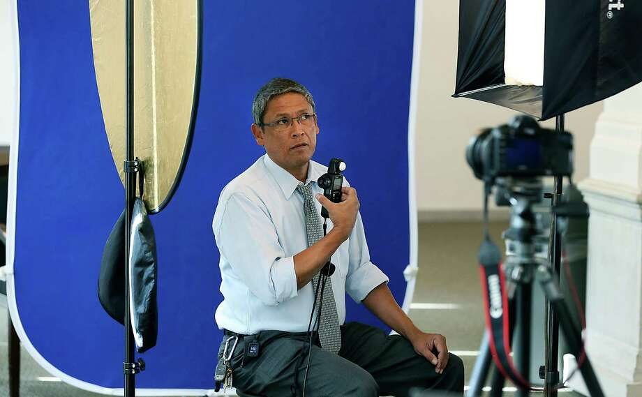 Fred Gonzales, the City of San Antonio Photographer, checks the lighting in a portable studio set up for portraits after a city council meeting. Tuesday, Dec. 16, 2014. Photo: BOB OWEN, San Antonio Express-News / © 2014 San Antonio Express-News