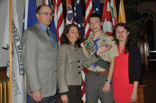 Christian Canham, second from right, of Troop 1 in Ballston Spa, gets his Eagle Scout Award at a Court of Honor held at the Ballston Spa United Methodist Church. With him are, from left, his father and mother Robert and Krista Canham and sister Haley Canham  The Eagle project was to design, attain funding and organize volunteer Boy Scouts and adults to build a 70-foot boardwalk in a muddy section of trail in Boyce Family Park, in Milton. (Glenn Harrison)