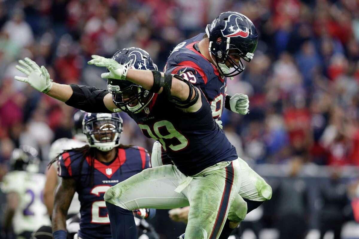 After sacking Ravens quarterback Joe Flacco, Texans defensive end J.J. Watt (left) celebrates with defensive end Jared Crick during the second half on Dec. 21, 2014, in Houston.