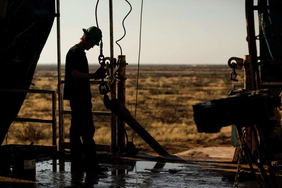 A worker waits to connect a drill bit outside Midland in the oil-rich Permian Basin of West Texas, which has enjoyed a boom that is turning sour as oil prices fall. In December, the state had a record 311,400 upstream oil and gas workers.  Photo: Brittany Sowacke / © 2014 Bloomberg Finance LP