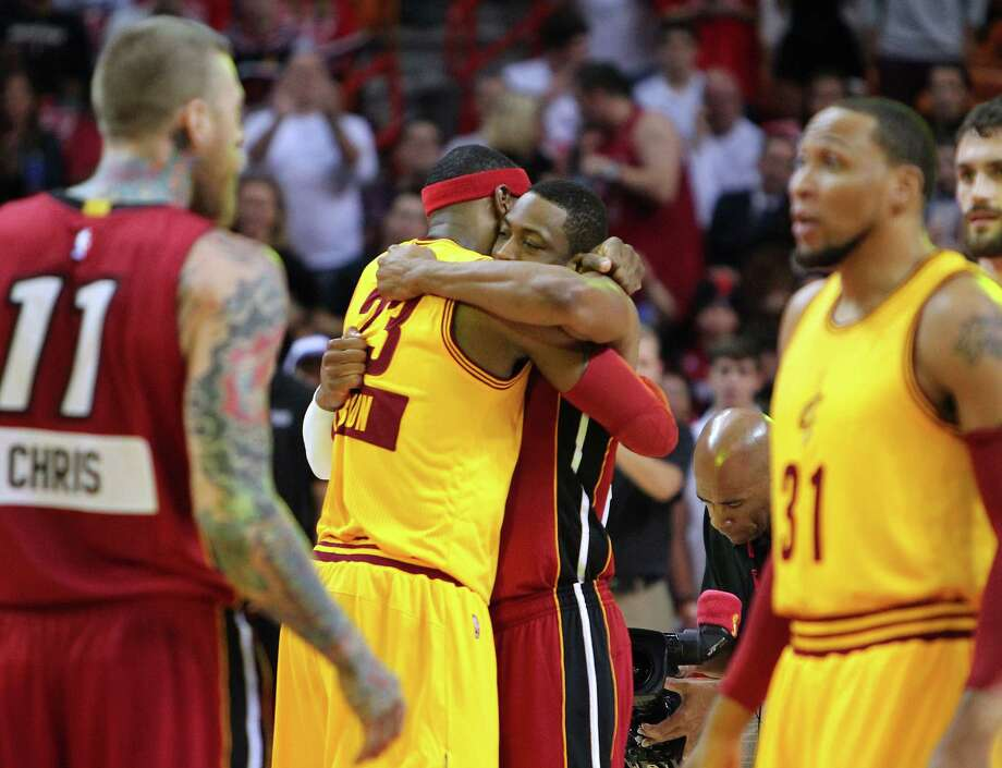 Cleveland's LeBron James (in yellow) gets a hug from Miami's Dwyane Wade before the teams met. The duo helped the Heat to two NBA titles. Photo: David Santiago / McClatchy-Tribune News Service / Miami Herald