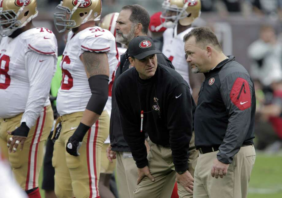 Offensive coordinator Greg Roman (right), talking with head coach Jim Harbaugh before a game, has drawn some indirect criticism. Two offensive tackles lamented getting away from the power run game. Photo: Carlos Avila Gonzalez / The Chronicle / ONLINE_YES