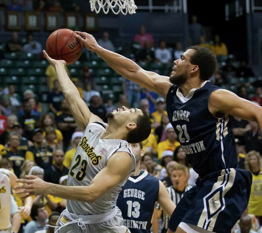 George Washington forward Kevin Larsen (21) goes up to block a shot by Wichita State guard Fred VanVleet (23) in the second half of an NCAA college basketball game at the Diamond Head Classic on Thursday, Dec. 25, 2014, in Honolulu. George Washington won 60-54 to take the tournament. (AP Photo/Eugene Tanner) Photo: Eugene Tanner / Associated Press / FR168001 AP