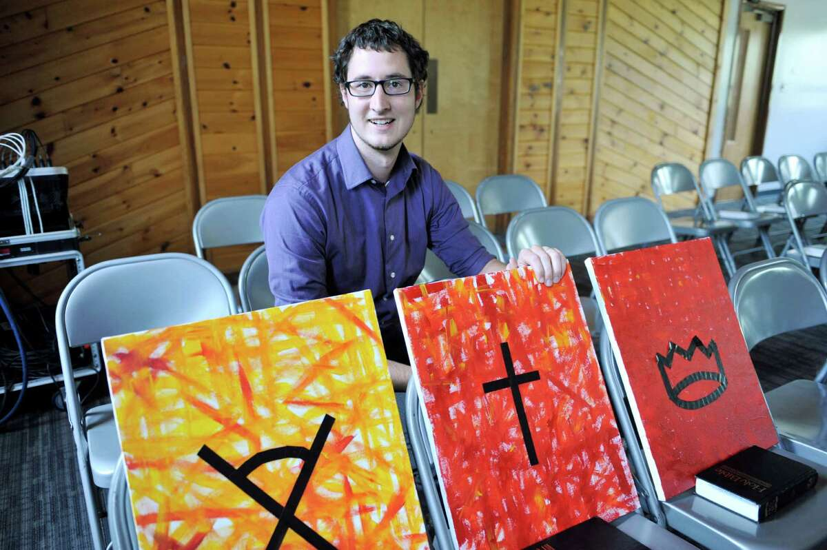 Assistant pastor at Delmar Lutheran Church, Josh Krepel, poses for a photograph with some of his paintings in the parish hall on Wednesday, Aug. 27, 2014, in Bethlehem, N.Y. The paintings will be hung in the parish hall where the contemporary worship services will be held. (Paul Buckowski / Times Union)