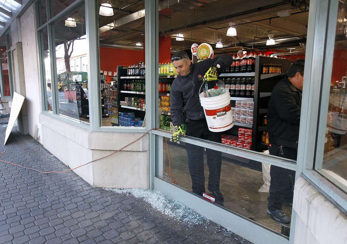 A restoration crew cleans up broken glass at the BevMo store at Jack London Square in Oakland, Calif. on Friday, Dec. 26, 2014 after vandals smashed storefront windows and damaged a decorated tree on Christmas night.