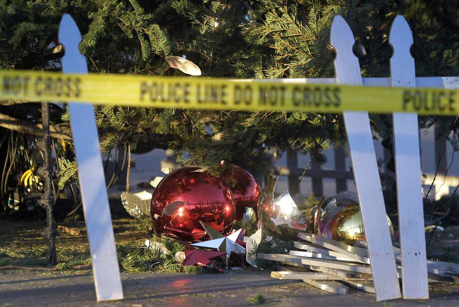 Yellow police tape surrounds broken ornaments piled under the Christmas tree at Jack London Square in Oakland, Calif. on Friday, Dec. 26, 2014 after vandals smashed storefront windows and damaged the holiday display on Christmas night. Photo: Paul Chinn, The Chronicle