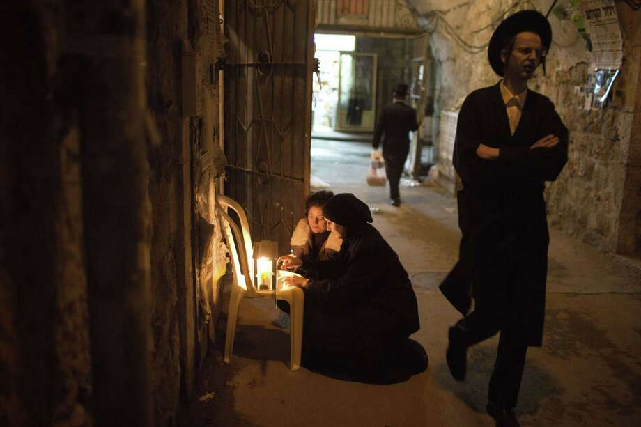 Ultra-orthodox women light candles Tuesday in Jerusalem on the last night of Hanukkah. Photo: MENAHEM KAHANA / AFP/Getty Images / AFP