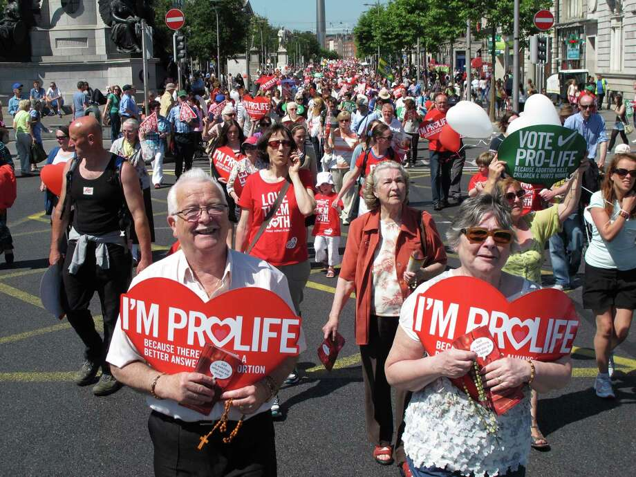 Stephen and Pauline O'Brien (foreground) hold Catholic rosary beads as they march through Ireland's capital, Dublin, in an antiabortion protest. Ireland is debating its constitutional ban on abortion again because of a case involving a brain-dead pregnant woman on life support. Family members want to turn off the woman's life support systems but doctors are refusing because the law requires them to defend the right to life of her 16-week-old fetus. Fetuses typically cannot survive outside the womb until around 24 weeks. Photo: Shawn Pogatchnik / Associated Press / AP