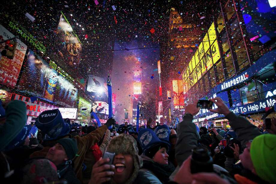 Revelers ring in 2014 in New York's Times Square. Most Americans look back on this year and shrug. Photo: John Minchillo / Associated Press / FR170537 AP