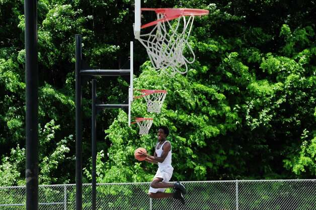 """Devon Jordan of Schenectady practices his basketball skills at Central Park on Monday, July 14, 2014, in Schenectady, N.Y.  Jordan moved to the area from Ohio a few months ago to be with his girl friend and says he will start Schenectady County Community College in the fall.  """"I plan to try out for the basketball team and I plan on making it, I'm up here every day practicing"""", Jordan said.  (Paul Buckowski / Times Union) Photo: Paul Buckowski, Albany Times Union / 00027773A"""