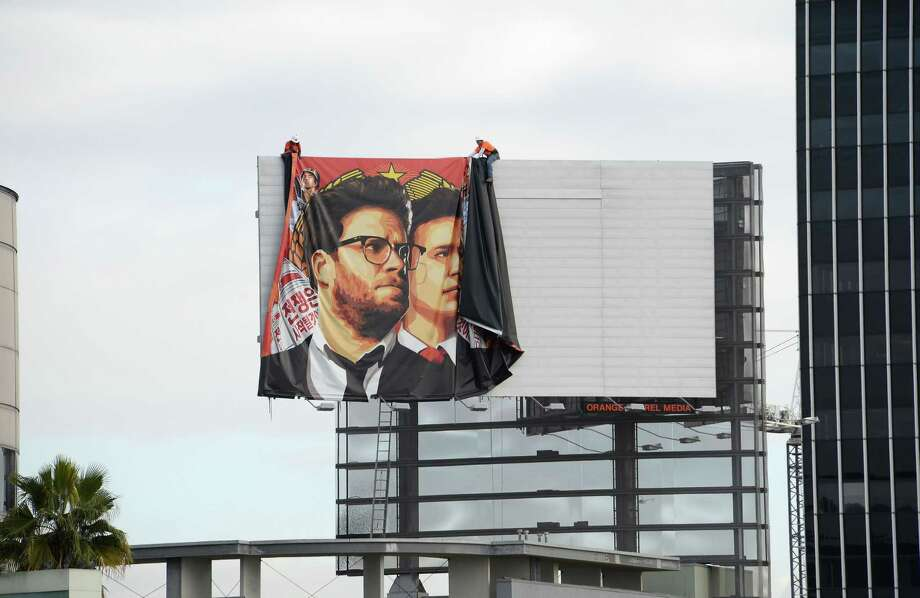 "TOPSHOTS Workers remove a poster-banner for ""The Interview"" from a billboard in Hollywood, California, December 18, 2014 a day after Sony announced it had no choice but to cancel the movie's Christmas release and pull it from theaters due to a credible threat.  Sony defended itself Thursday against a flood of criticism for canceling the movie which angered North Korea and triggered a massive cyber-attack, as the crisis took a wider diplomatic turn.   AFP PHOTO / ROBYN BECKROBYN BECK/AFP/Getty Images Photo: ROBYN BECK / AFP/Getty Images / AFP"