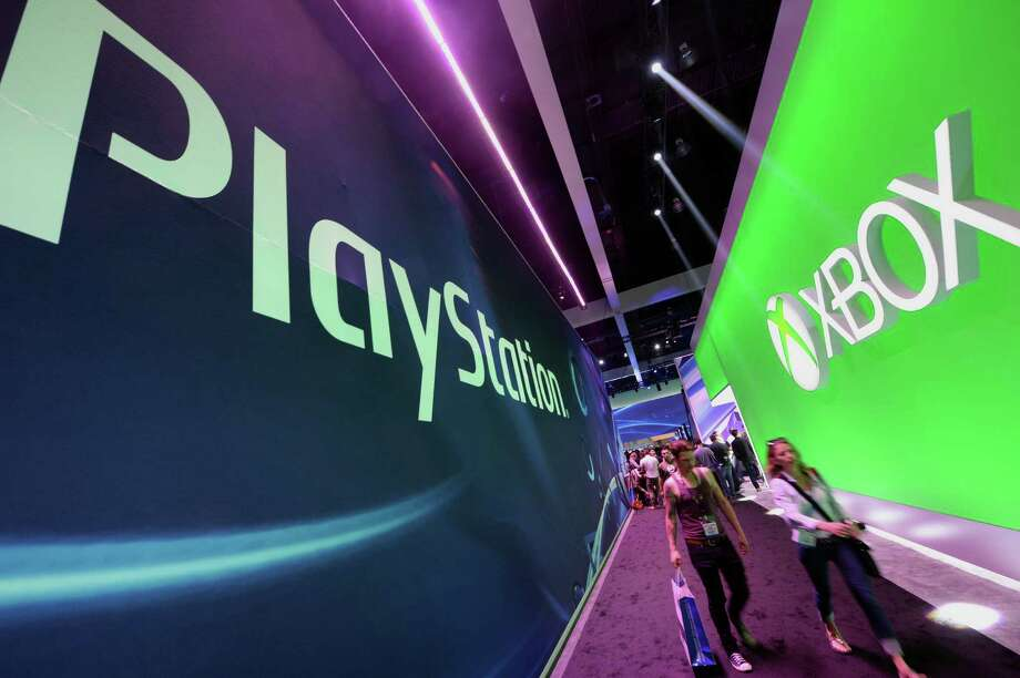 Attendees walk between signs for Sony PlayStation and Microsoft XBox on the first day of the Electronic Entertainment Expo (E3) in Los Angeles, California, June 11, 2013.   The Electronic Entertainment Expo (E3), an annual trade fair for the computer and video games industry, runs from June 11-13. AFP PHOTO / ROBYN BECKROBYN BECK/AFP/Getty Images Photo: ROBYN BECK / AFP/Getty Images / AFP