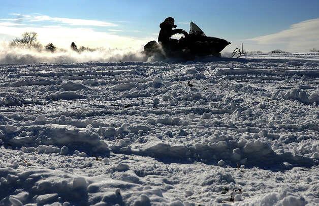 Nicholas Marshall, 13, of Delmar enjoys the new fallen snow on his snowmobile in a field by his home on Friday, Jan. 3, 2014 in Delmar, N.Y. (Lori Van Buren / Times Union) Photo: Lori Van Buren, Albany Times Union / 00025215A