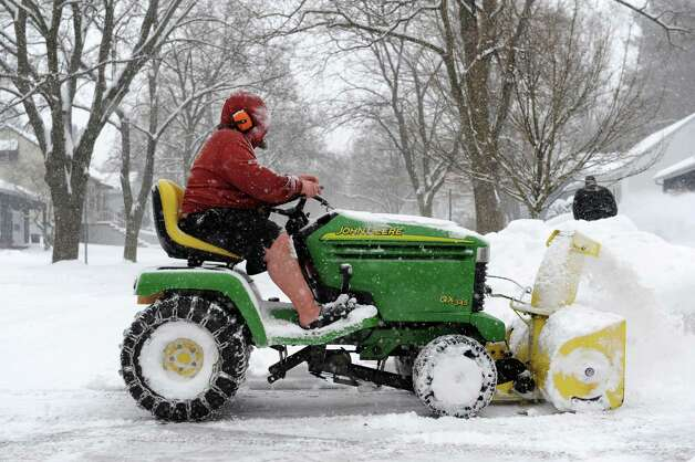 Brian Chakurmanian of Guilderland wears shorts as he does the good neighbor chore of plowing out the driveways of elderly neighbors on Norwood St. Wednesday, Feb. 5, 2014 in Albany, N.Y.  (Lori Van Buren / Times Union) Photo: Lori Van Buren, Albany Times Union / 00025615A