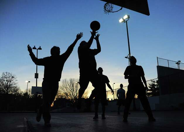 Young men play a pick-up game of basketball in Washington Park as the sun goes down on Monday, Nov. 10, 2014 in Albany, N.Y.  (Lori Van Buren / Times Union) Photo: Lori Van Buren, Albany Times Union
