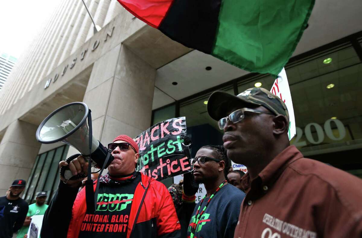 Kofi Taharka, left, of the National Black United Front, along with other demonstrators gather in protest of the Harris County Grand Jury's decision not to indict a Houston Police Department officer who killed Jordan Baker at the Houston Police Department Headquarters Friday, Dec. 26, 2014, in Houston, Texas.