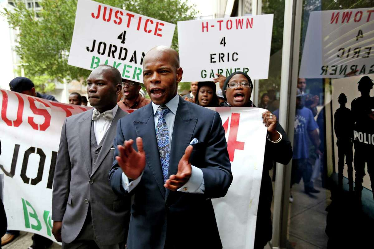 Deric Muhammad, an activist, along with demonstrators march in protest of the Harris County Grand Jury's decision not to indict a Houston Police Department officer who killed Jordan Baker at the Houston Police Department Headquarters Friday, Dec. 26, 2014, in Houston, Texas.