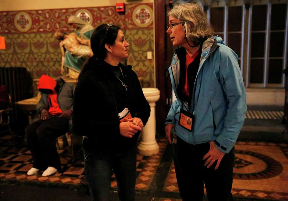 Laura Slattery (right), executive director of the Gubbio Project, confers with program manager Tina Christopher at St. Boniface Catholic Church. Photo: Leah Millis / The Chronicle / ONLINE_YES