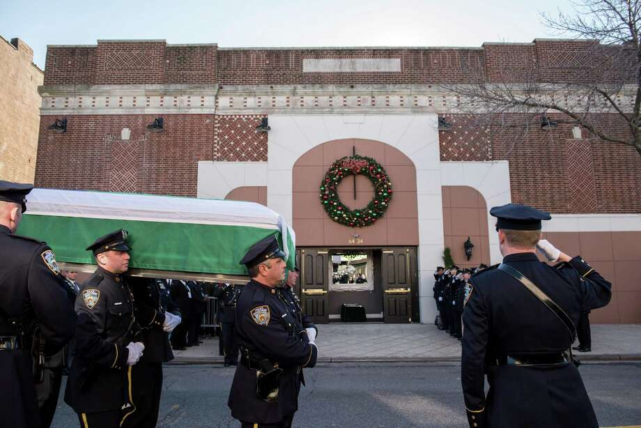 New York police officers bear the casket of fallen colleague, Rafael Ramos, to Christ Tabernacle Church in the Glendale neighborhood of New York. Ramos and his patrol partner, Wenjian Liu, were fatally shot on Dec. 20 by a man who had announced his intent to target officers in retaliation for the recent deaths of unarmed black men. Photo: ANDREW RENNEISEN / New York Times / NYTNS